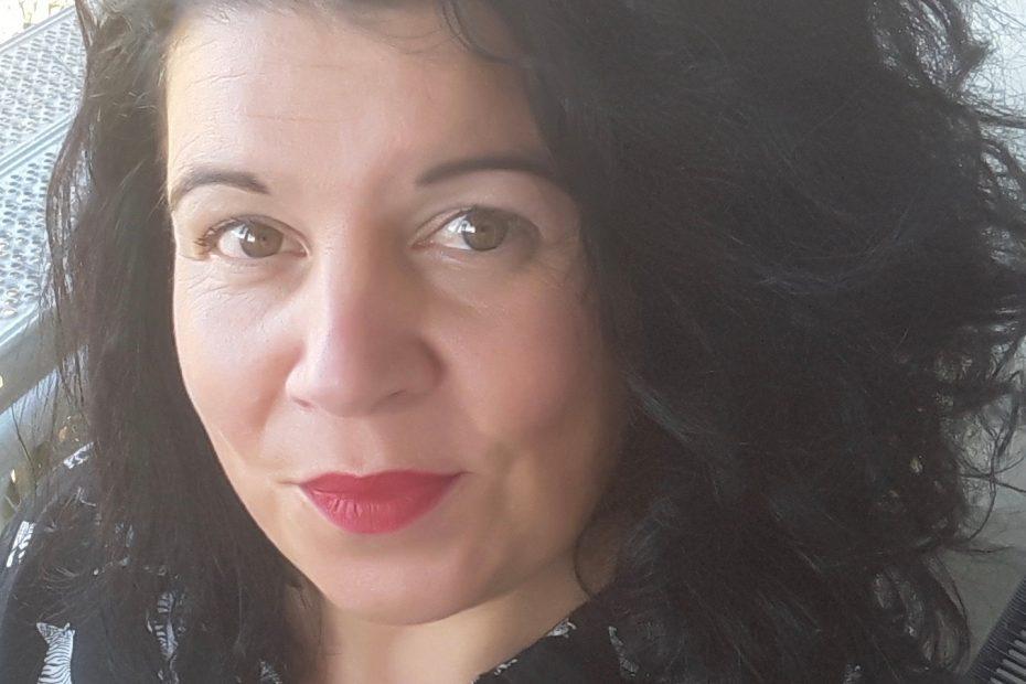 Foto van Lieke tegen een lichte achtergrond. Lieke heeft schouderlang, donker, krullend haar, rode lipstick en draagt een zwarte blouse met daarop afbeeldingen van kleine witte getekende zebra's in diverse houdingen.